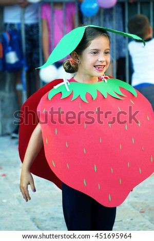 Montenegro, Herceg Novi - 04/06/2016: Girl showing strawberry on a masquerade. 10 International Children's Carnival
