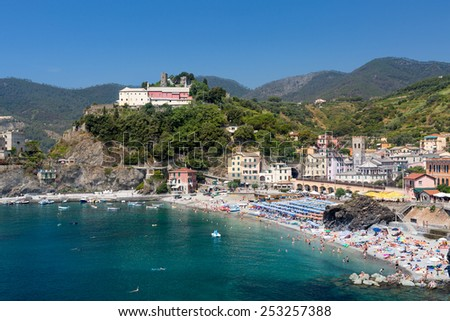 Monterosso al Mare, a coastal village and resort part of Cinque Terre, Italy. Unrecognizable people sunbathe on a sunny summer day - stock photo