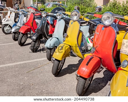 """MONTIANO, FC, ITALY - MAY 25: row of vintage italian scooters Vespa and Lambretta parked during the rally """"Vespagiro"""" on May 25, 2014 in Montiano, FC, Italy  - stock photo"""