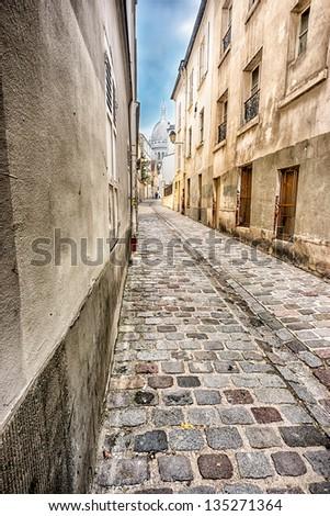 Montmartre street and The Basilica of the Sacred Heart behind in Paris, France  (Basilique du Sacré-Cœur) - stock photo