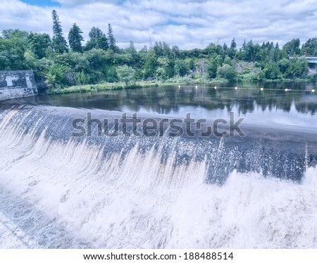 Montmorency Falls with a cloudy sky near Quebec City. Vintage filter - stock photo