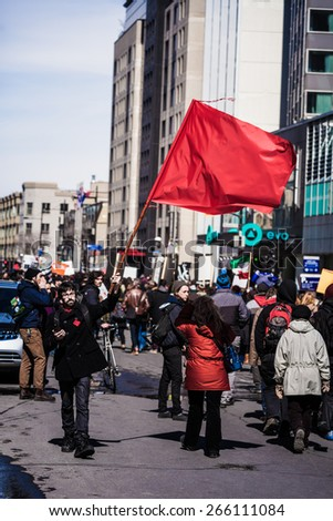 MONTREAL, CANADA   APRIL 02 2015: Riot in the Montreal Streets to counter the Economic Austerity Measures. Protester Agitating a Red Flag in the Street - stock photo