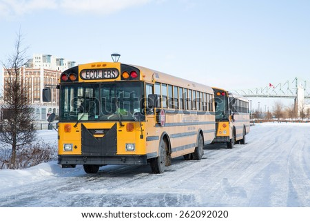 MONTREAL, CANADA - 16 JAN: School buses parked up in the snow and ice wait to collect school children. Montreal, Canada, on 16th January 2015 - stock photo