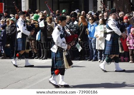 MONTREAL, CANADA - MARCH 20: Irishmen in their kilt playing their bagpipes during the St. Patrick's Day Parade on March 20, 2011 in Montreal, Canada. It's a traditional Irish holiday parade.
