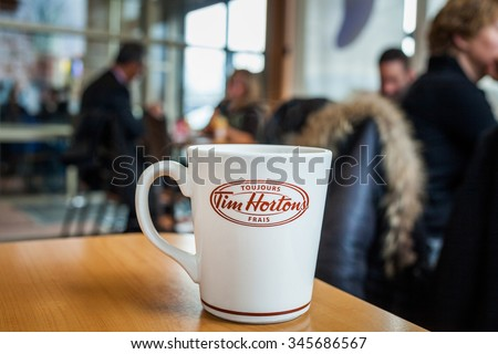 Montreal, CANADA - November 30th 2015:Fresh French Coffee Cup on a Table Inside a Time Hortons Restaurant in the Morning with Consumers in the Background