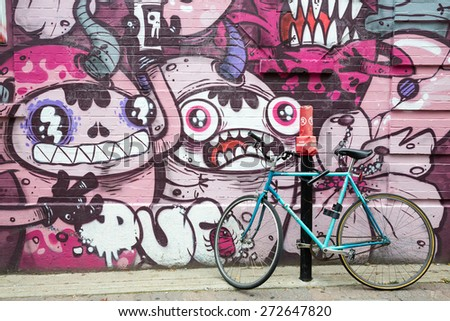 MONTREAL CANADA SEPT 5: Parked bike and graffiti on the streets of Montreal. Urban street art is very popular within the city.  In Montreal on Sept 5th 2014 - stock photo