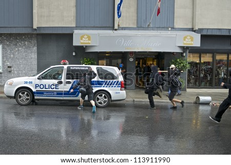 MONTREAL, CANADA - SEPTEMBER 22: Unidentified protesters attack a police vehicle during a march for free tuition that turned violent on September 22, 2012 in Montreal. - stock photo