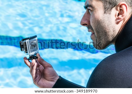 MONTREAL, CIRCA JUNE 2014 - Two Hot Spring Days of Freediving Competition at Jean-Drapeau 50m Outdoor Olympic Pool. Member of the Staff Filming the Official Performance with a GoPro Camera - stock photo