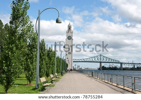 Montreal clock tower located at the entrance of the old port of the city. Also called Victoria Pier or Sailors Memorial Clock. In the background Jacques Cartier bridge. - stock photo