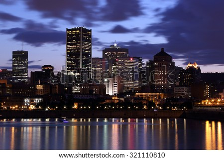 Montreal Downtown Panorama at sunset. Montreal reflected on the river at dusk with city lights and urban buildings. Montreal over river at sunset with city lights. Montreal reflected in water.  - stock photo