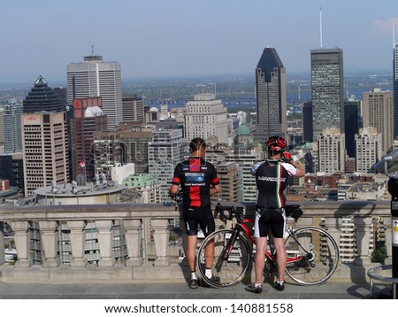 MONTREAL - JUNE 2:  Cyclists pause to admire the view from the top of Mount Royal during the annual Tour de l'Ile bike ride in Montreal on June 2, 2013. - stock photo