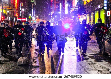 MONTREAL - MARCH 27: Police in heavy riot gear charge at a crowd of protesters during an anti-austerity demonstration on March 27, 2015 in Montreal, Quebec. - stock photo