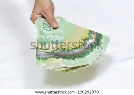 MONTREAL - NOVEMBER 19: A hand holding some fanned out twenty dollar Canadian bills is photographed on November 19, 2012 in Montreal, Quebec, Canada. - stock photo