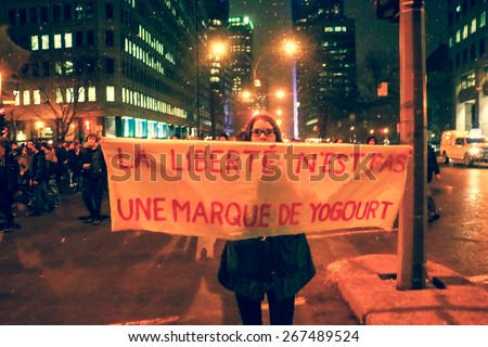 MONTREAL - Over 50,000 students are on strike in Quebec. A young woman holds up a hand-painted sign during a protest in Montreal. - stock photo
