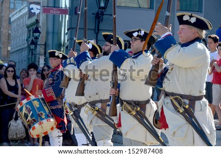 MONTREAL QUEBEC CANADA AUGUST 24: Men as soldiers re-enacting New France period in Old Montreal, Pointe-a-Calliere's 18th Century Public Market on august 24 2013 in Montreal Canada - stock photo