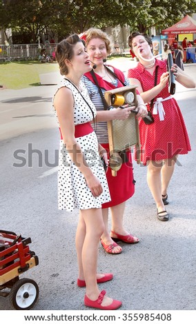 Montreal Quebec Canada - July 20 2014 Acapella washboard trio ladies in old fashioned hair and retro 60's clothing and singing old style music on the street at Festival Just For Laughs