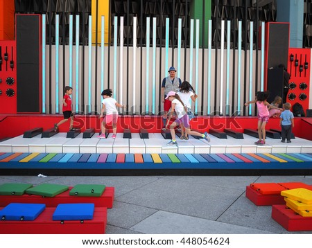 Montreal Quebec Canada 30 June 2016 Children playing on giant sized piano and other instrument at the Jazz Festival kids musical playground