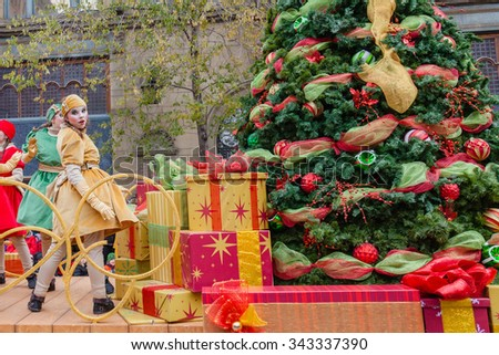 MONTREAL, QUEBEC, CANADA - NOVEMBER 21, 2015 : Girl near Christmas Tree in the 65th edition of the Santa Claus Parade Destination Centre-ville (Defile du Pere Noel) along Saint Catherine Street. - stock photo