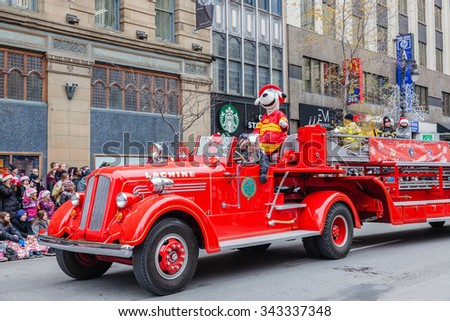 MONTREAL, QUEBEC, CANADA - NOVEMBER 21, 2015 : Old retro fire car in the 65th edition of the Santa Claus Parade Destination Centre-ville (Defile du Pere Noel) along Saint Catherine Street. - stock photo