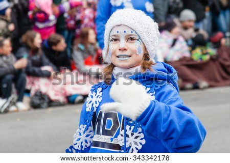 MONTREAL, QUEBEC, CANADA - NOVEMBER 21, 2015 : Snowflake little girl in the 65th edition of the Santa Claus Parade Destination Centre-ville (Defile du Pere Noel) along Saint Catherine Street. - stock photo