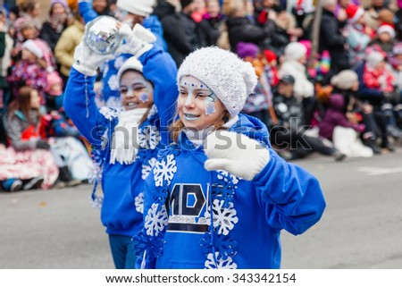 MONTREAL, QUEBEC, CANADA - NOVEMBER 21, 2015 : Snowflake little girls in the 65th edition of the Santa Claus Parade Destination Centre-ville (Defile du Pere Noel) along Saint Catherine Street. - stock photo