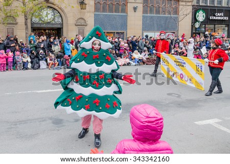 MONTREAL, QUEBEC, CANADA - NOVEMBER 21, 2015 : Woman in Christmas Tree costume in 65th edition of the Santa Claus Parade Destination Centre-ville (Defile du Pere Noel) along Saint Catherine Street. - stock photo