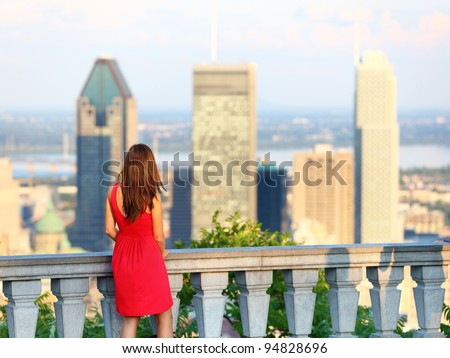 Montreal. Woman looking at Montreal downtown skyline cityscape. Tourist girl in red dress on Mont Royal in spring or summer. - stock photo