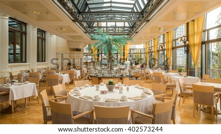 Montreux, Switzerland - April 6, 2016: Interior of Breakfast restaurant with big windows, glass roof in Fairmont Le Montreux Palace 5 stars Luxury Hotel Resort Spa in the morning - stock photo