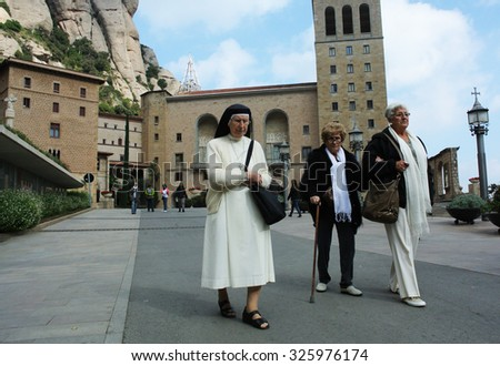 MONTSERRAT, SPAIN - OCTOBER 25, 2014: Every day, hundreds of people travel to the top of the mountain to visit Santa Maria de Montserrat abbey in Montserrat, Catalonia, Spain, Oct.25, 2014. - stock photo