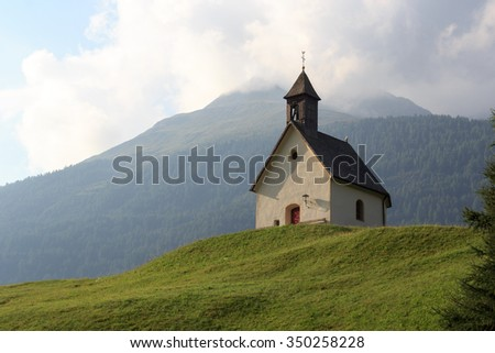 "Monument holy spirit chapel with German text ""Holy Spirit fills our hearts"" on the door in alpine village Bichl with mountain, Austria - stock photo"