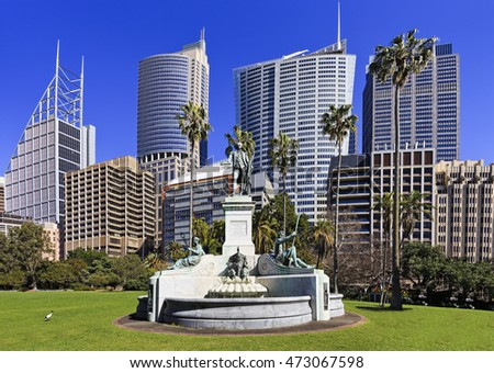 Monument of Captain Arthur Philip - first governor of NSW colony of Sydney in Royal Botanic Garden against modern city skyscraper towers.