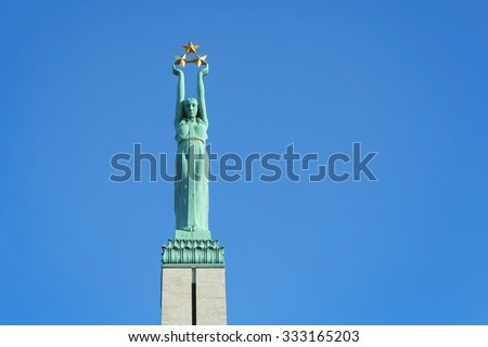 Monument of freedom in Riga. Woman holding three gold stars which symbolise three regions of Latvia.