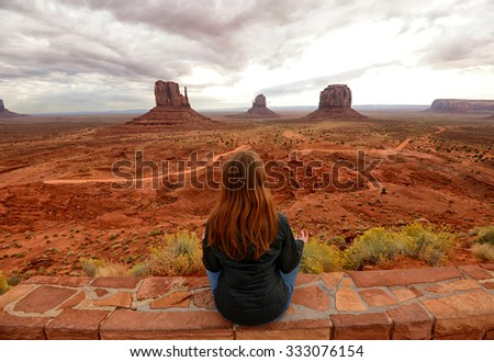 Monument Valley and woman meditating in front of monument valley - stock photo