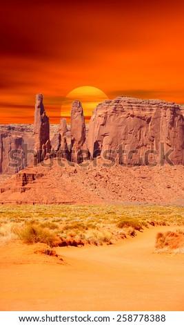 Monument Valley Arizona with orange setting sun - stock photo