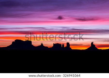Monument Valley at sunrise. (silhouette) - stock photo