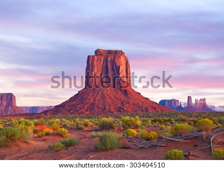 Monument Valley in Utah and Arizona, sunrise or sunset with dramatic clouds, desert landscape of Navajo Nation Park is a famous travel destination for it's red rock formations  - stock photo