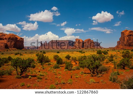 Monument Valley landscape with vegetation and clouds in the blue - stock photo