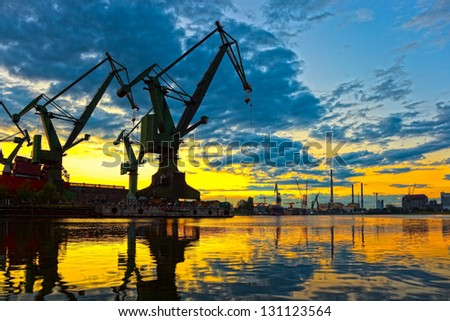 Monumental Cranes at sunset in Shipyard. - stock photo