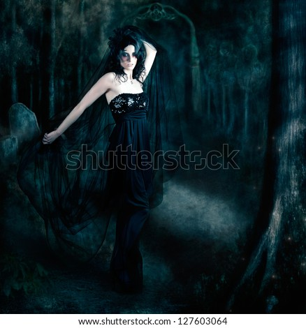 Moody atmospheric portrait of an elegant mysterious woman posing in a black evening gown amongst the shadows of darkness - stock photo