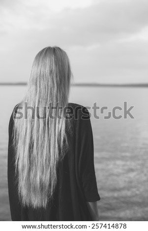 Moody, black and white portrait of woman looking at distance - stock photo