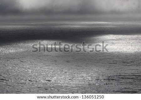 Moody Cloudscape and Shadows over Ocean - stock photo