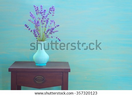 Moody Cyan Blue Toned Artsy Lavender Bouquet in Blue Vase on a Vintage Side Table against rustic Turquoise Wood Board Background with room or space for copy, text, your words.  Horizontal modern style