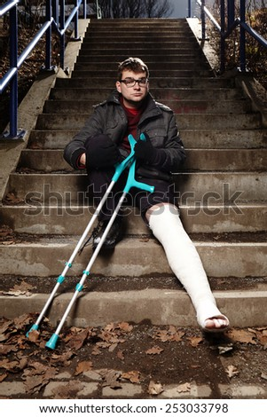 Moody man with broken leg - stock photo