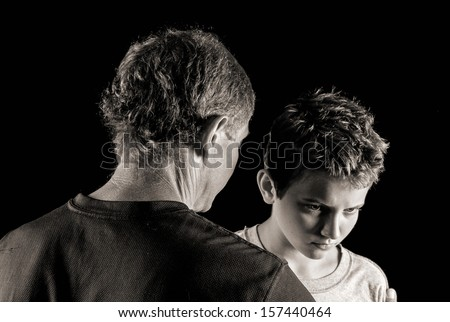 moody monochrome portrait of father-son trouble: father tries to reason with (or scold, or comfort) his defiant son - stock photo