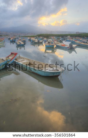 Moody morning landscape of Tamsui river in Taipei Taiwan, with stranded boats during a low tide ~ Scenery of beautiful sunrise by Tamsui River, Taipei Taiwan - stock photo
