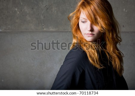 Moody portrait of a beautiful fashionable young redhead girl with contemplative expression.