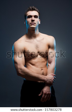 Moody portrait of a very fit lean young brunette man. - stock photo