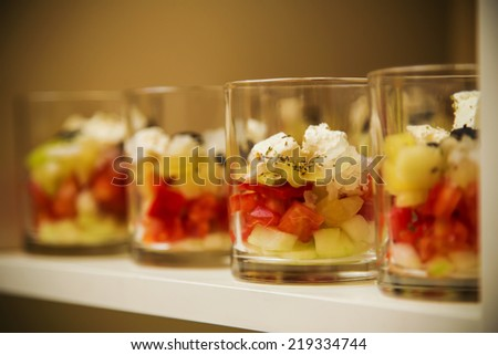 Moody shot of banquet salad served in glass. Tomato, red and green pepper, cucumber, onion and cream cheese. See more in my gallery - stock photo