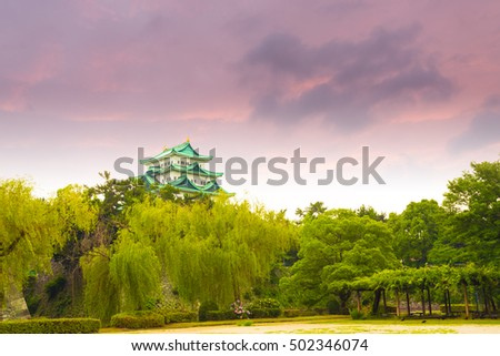 Moody sunset clouds hover above Nagoya Castle stronghold over a green treeline in Japan