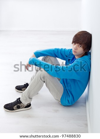 Moody teenager sitting by the wall on the floor - stock photo